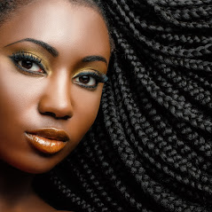 Extreme close up beauty portrait of young african woman showing long braided hair next to face.